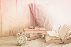 Clock. Alarm clock on bed with book and glasses at morning time stock image