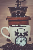 Clock Alarm on Coffee beans. Coffee cup full of coffee beans Stock Image