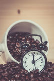 Clock Alarm on Coffee beans. Coffee cup full of coffee beans Royalty Free Stock Photo