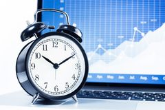 Clock alarm with stock graph chart in laptop screen background royalty free stock photography