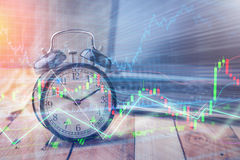 Clock alarm with stock graph chart in laptop screen background.Time,stock market,business success and investment concept. stock image