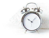 Alarm clock and white pillow Stock Photo