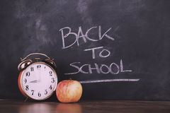 Clock and an apple against a blackboard Vintage Retro Filter. Royalty Free Stock Photography