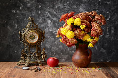 Clock, apples and flowers in a ceramic vase Stock Image