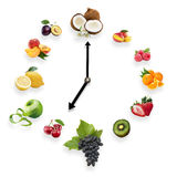 Clock arranged from healthy fruits isolated on white background. Food clock with fruits. Healthy food concept stock images