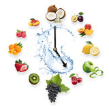 Clock arranged from healthy fruits splash by water isolated on w. Hite background. Food clock with fruits. Healthy food concept Royalty Free Stock Image