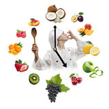 Clock arranged from healthy fruits with young boy dressed as che Stock Images