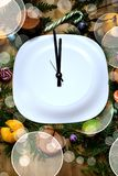 Clock arrows on a white plate surrounded by Christmas attributes. Concept of New Year coming Royalty Free Stock Photo