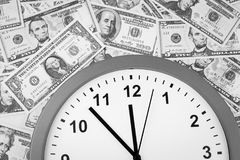 Time is money. Clock on assorted American banknotes. Time is money idea Stock Photo
