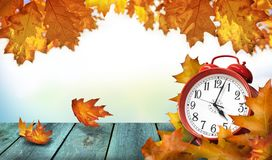 Clock and autumn leaves on wooden table - daylight saving time c. Clock and autumn leaves on the wooden table - daylight saving time concept stock image