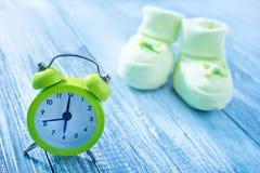 Clock and baby socks Stock Photos