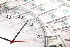 Clock on the background of banknotes dollars Stock Photo