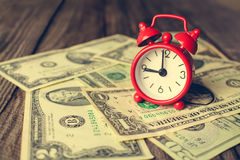 Clock on background of dollars. Concept of money is time. Toned image Stock Photography