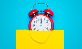 Clock in bag. Red alarm clock in the beautiful yellow shopping bag on the wonderful blue background Royalty Free Stock Photos