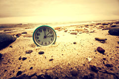 Clock on the beach. Time and business concept. Stock Image
