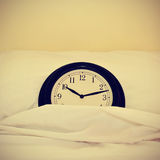 Clock in bed, with a retro effect Stock Photo