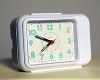 Clock. A bed side alarm clock. White with turquoise numbers Royalty Free Stock Image