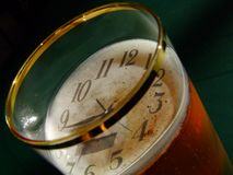 Clock and beer. Time is stopped in a glass of beer or not? It is maybe an illusion when you drink too much or it is just a wish - to sink the time Royalty Free Stock Photo
