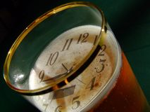 Clock and beer. Time is stopped in a glass of beer or not? It is maybe an illusion when you drink too much or it is just a wish - to sink the time Stock Images