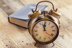 Clock and Bible on wood Royalty Free Stock Photography