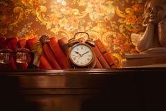 Clock on the bookshelf. Vintage clock on the bookshelf. The watch is made of yellow metal. On a shelf a few old books, cherub figurine. Background - Vintage Stock Photo