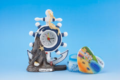 Clock and box - sea attributes. Clock and box souvenir from Italy on blue background Royalty Free Stock Photos