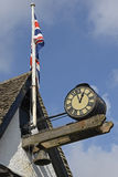 Clock and British flag at Burford, England Stock Images