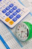 Clock and calculator on data. A clock and calculator on data sheet, means time and investment increasing, or insurance time analysis, important time and Royalty Free Stock Photography