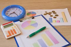 Clock, calculator, graphics, small change on table. business strategy as concept Royalty Free Stock Photo