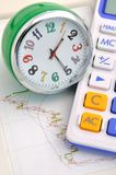 Clock and calculator on stock graph. A clock and calculator on stock graph sheet, means time and stock value increasing, or stock marketing anaysis, important Stock Photography