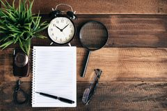 Clock, camera, magnifying glass, blank notebook on wooden table Royalty Free Stock Images
