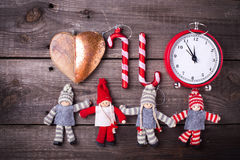 Clock, candy canes and decorative dollies on aged  wooden backg Stock Images