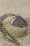 Clock with chain on sand. Royalty Free Stock Images
