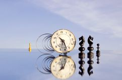 Clock and chessmans on mirror Royalty Free Stock Images