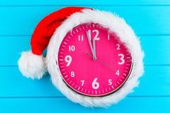 Clock with christmas santa hat Stock Image