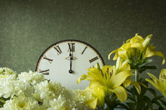 Clock, chrysanthemums and lilies. 12 hours. Antique clock with Roman numerals, chrysanthemums and lilies. 12 hours Royalty Free Stock Photo