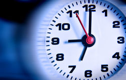Clock close up over blue and black background. Deadline concept Royalty Free Stock Images