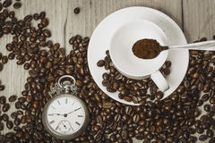 clock and coffee beans on a wooden table Royalty Free Stock Image