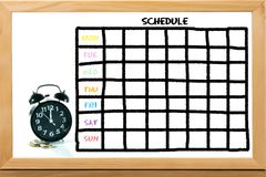 Clock and coins with Schedule. With grid time table on white board background royalty free stock image