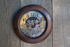 Clock with coins. On the wooden background Stock Images