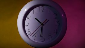 Clock on color wooden plank wall, night Light. Clock on color wooden plank wall. white office clock on colorful background. night. slow motion stock footage