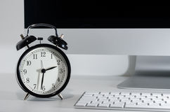 Clock on computer desk Royalty Free Stock Photos