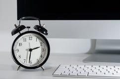 Clock on computer desk Royalty Free Stock Photos