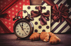 Clock with croissant on a table. Royalty Free Stock Image