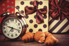 Clock with croissant on a table. Stock Image