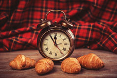 Clock with croissant on a table. Stock Photos