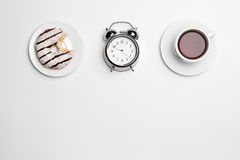 The clock, cup, cake on white background Royalty Free Stock Photos