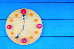 Clock dial made from radish and carrot Royalty Free Stock Images