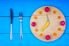 Clock dial made from vegetables with fork and knife Stock Photography
