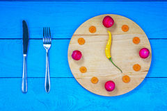 Clock dial made from vegetables with knife and fork Royalty Free Stock Photo